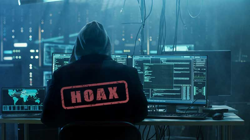 Hacker sitting at desk with the word HOAX in red stamped on his back sending email scam